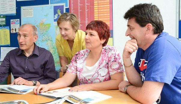 profesora y 3 estudiantes estudiando un cursos de inglés para principiantes en el extranjero