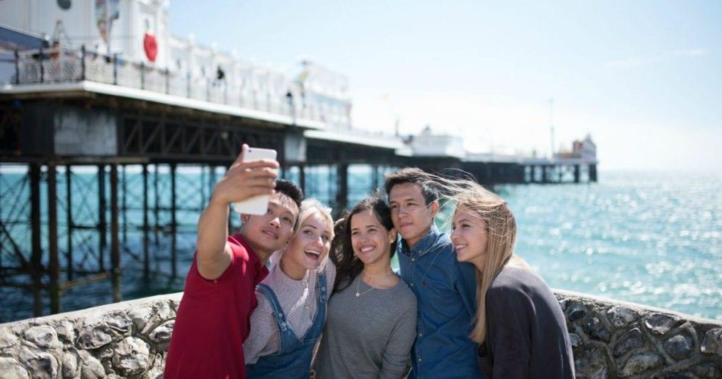 estudiantes de inglés en Brighton B2 C1, sacando un selfie con el muelle al fondo