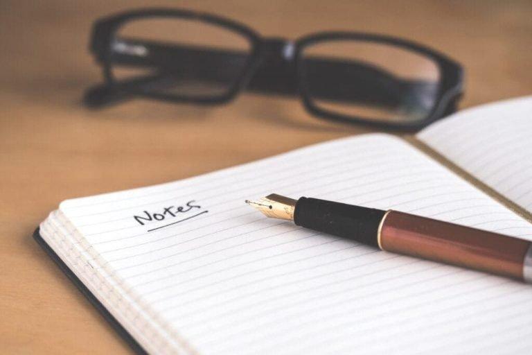 un bolígrafo, cuaderno y gafas de un profesor   enseñar inglés online