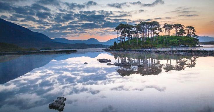 Puesta de sol y nubes grises sobre un lago y una isla, Galway, Irlanda