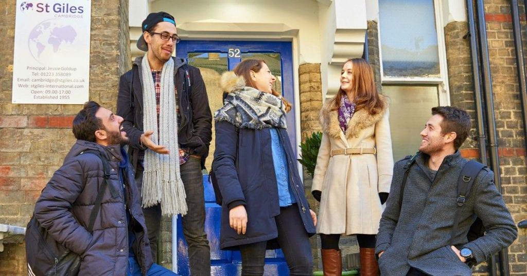 Estudiantes de inglés charlando por la entrada de su escuela