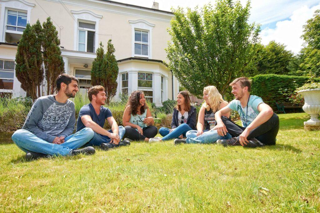 Seis estudiantes felices sentados en el césped con la escuela de inglés en Eastbourne detrás.