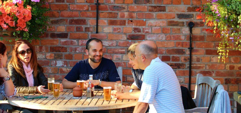 estudiantes charlando y tomando bebidas a través cursos de inglés en el extranjero para adultos